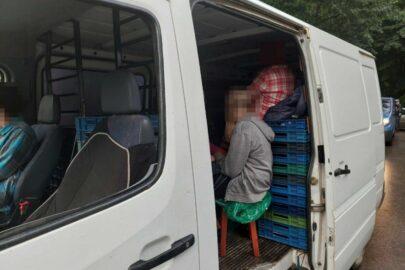 7 osób na taboretach i skrzynkach w ładowni Mercedesa Sprintera